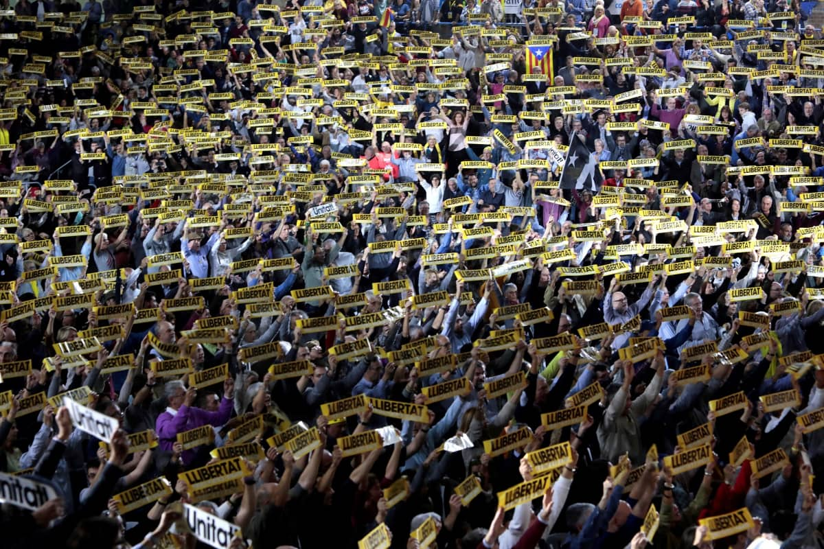 Mielenosoittajat nostavat ylös keltaisia nauhoja, joissa lukee vapaus.