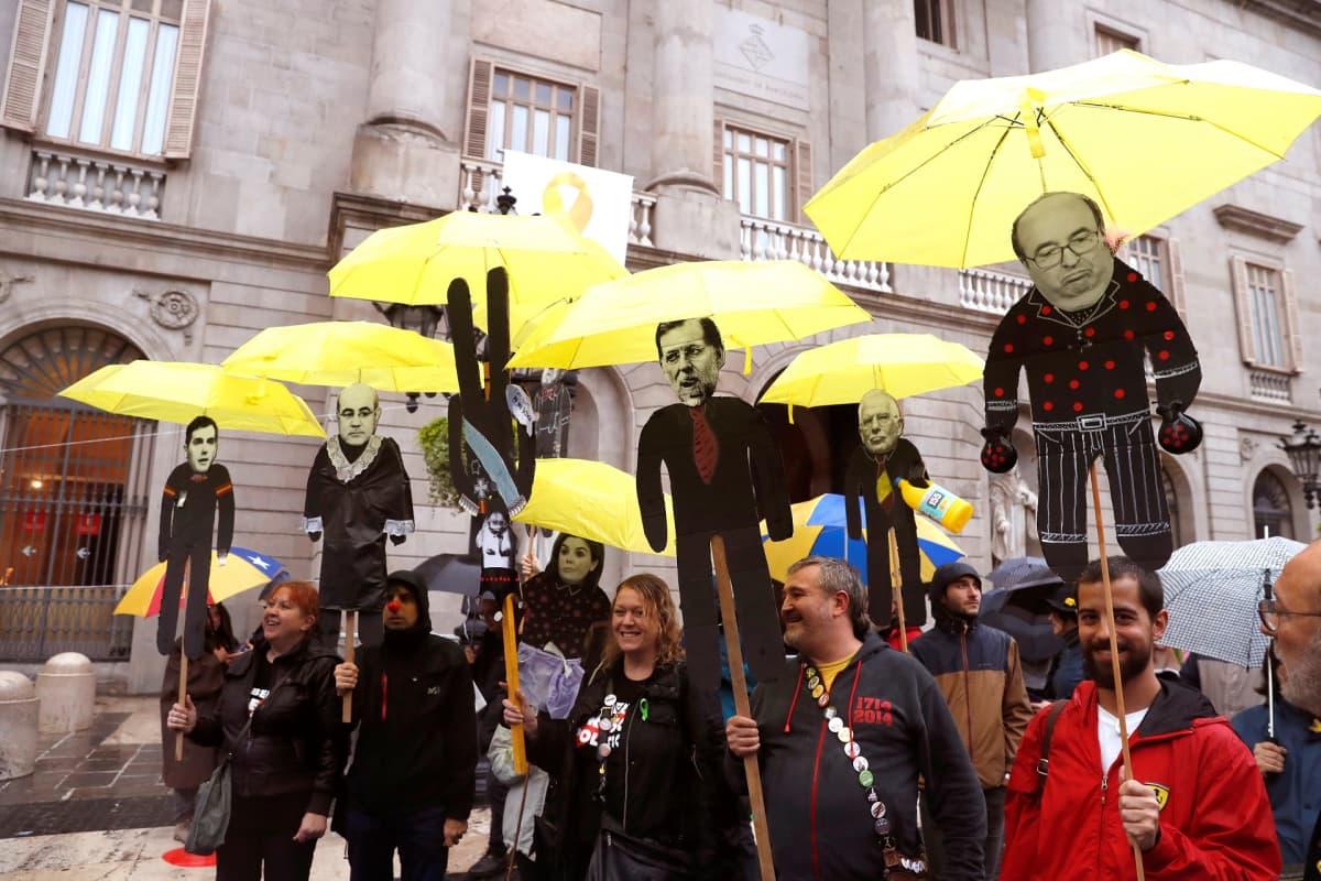 Mielenosoittajat kantoivat lauantaina poliitikkojen hahmoja sateenvarjojensa alla Barcelonassa.