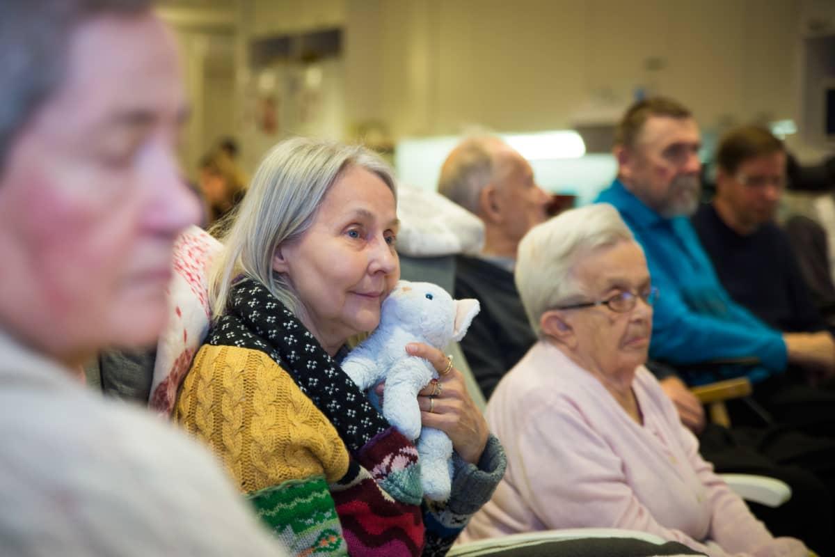 69-vuotias Maria Sandvik nauttii musiikista pehmolelukissan kanssa.