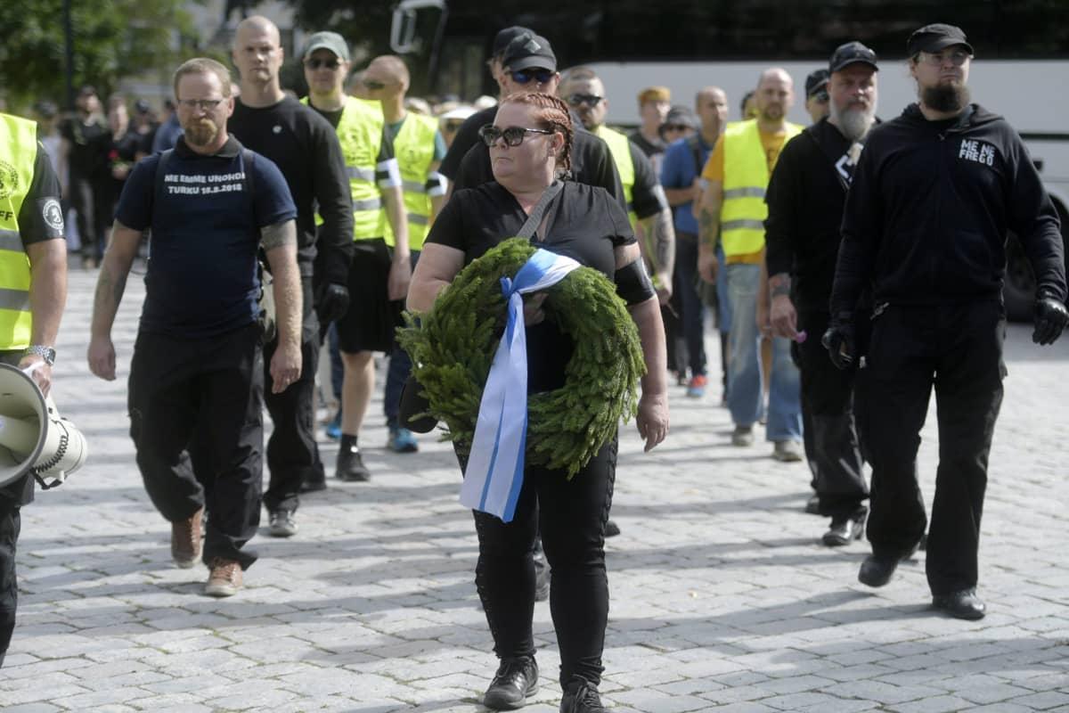 Kansallismielisten liittouman 188-Kukkavirta-muistokulkue Turussa lauantaina 18. elokuuta 2018, etummaisena seppeleen kanssa Terhi Kiemunki sekä liikkeen johtohahmo Antti Niemi (vas.).