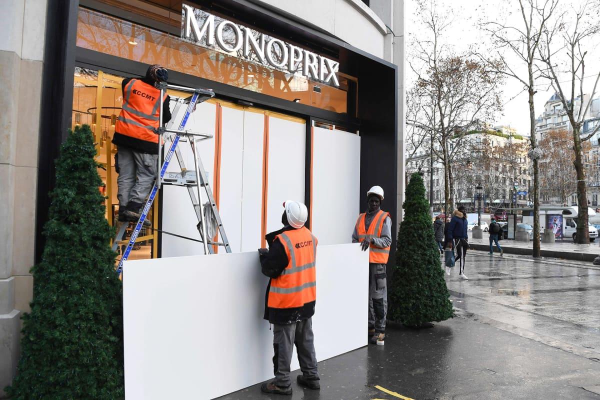 Työntekijät suojaavat näyteikkunoita Champs-Elyseellä perjantaina tulevan mielenosoituksen takia.