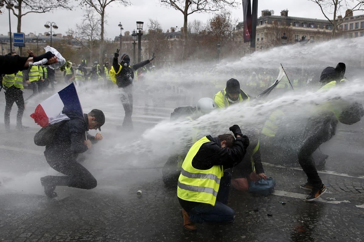 Mielenosoittajia ruiskutetaan vesitykeillä 1. joulukuuta.