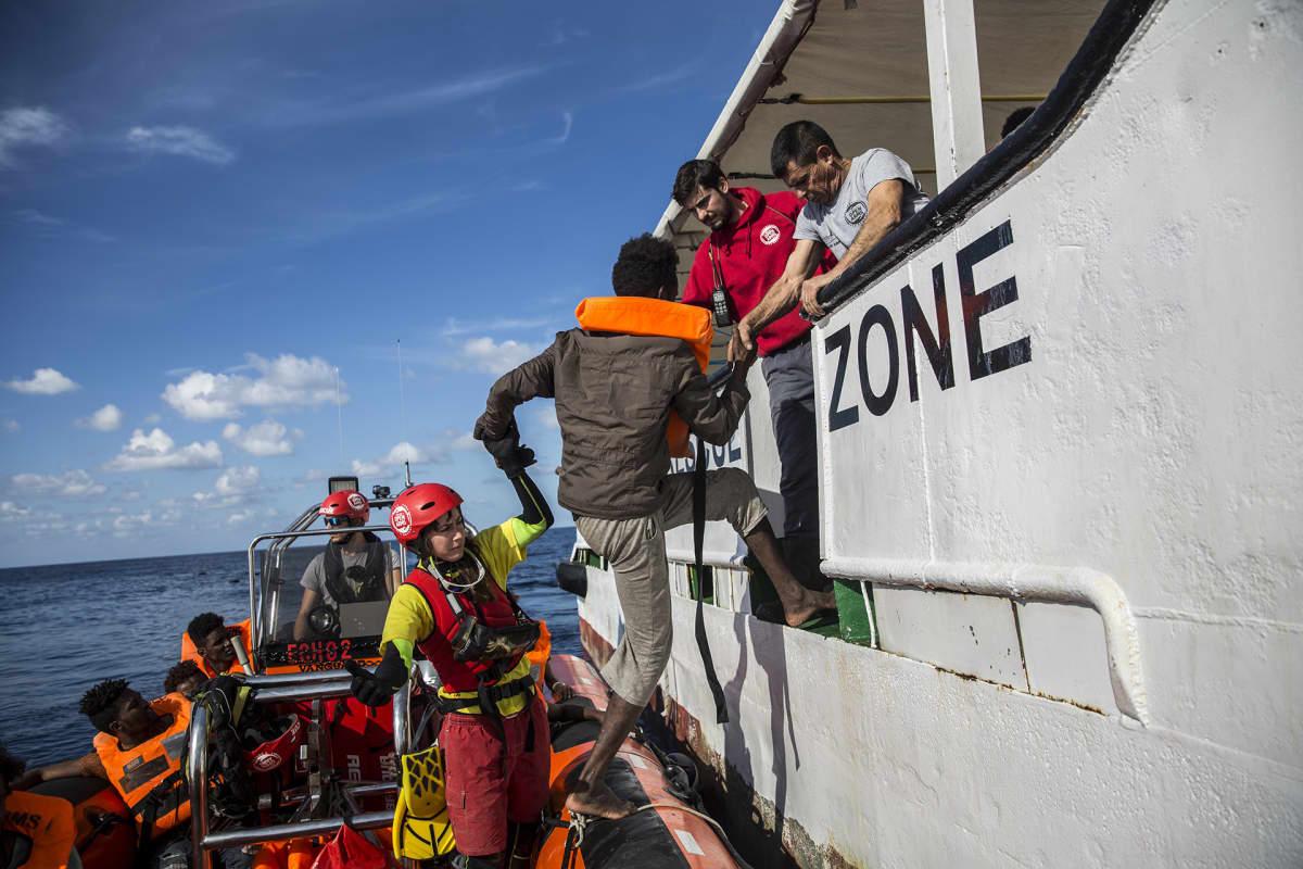 Pakolaista autetaan laivaan.