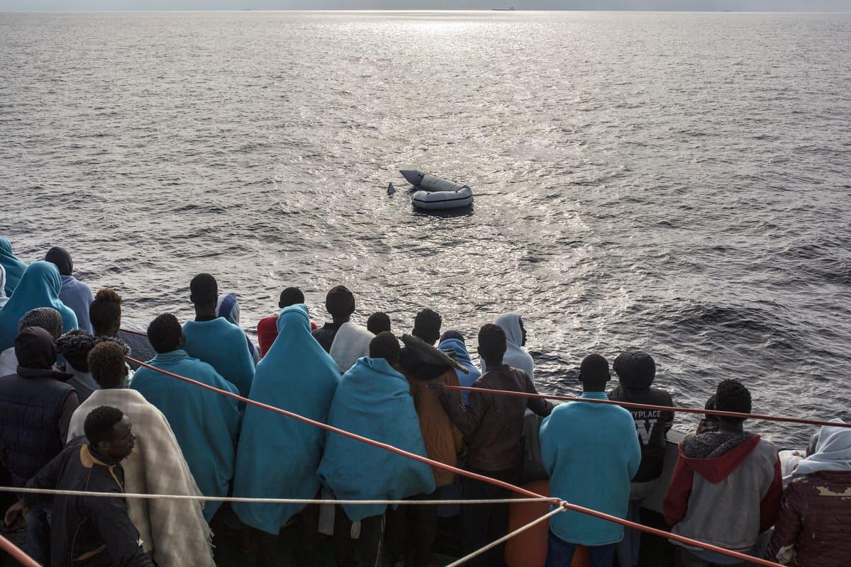 Pelastetut katsovat pelastuslauttaa vedessä.
