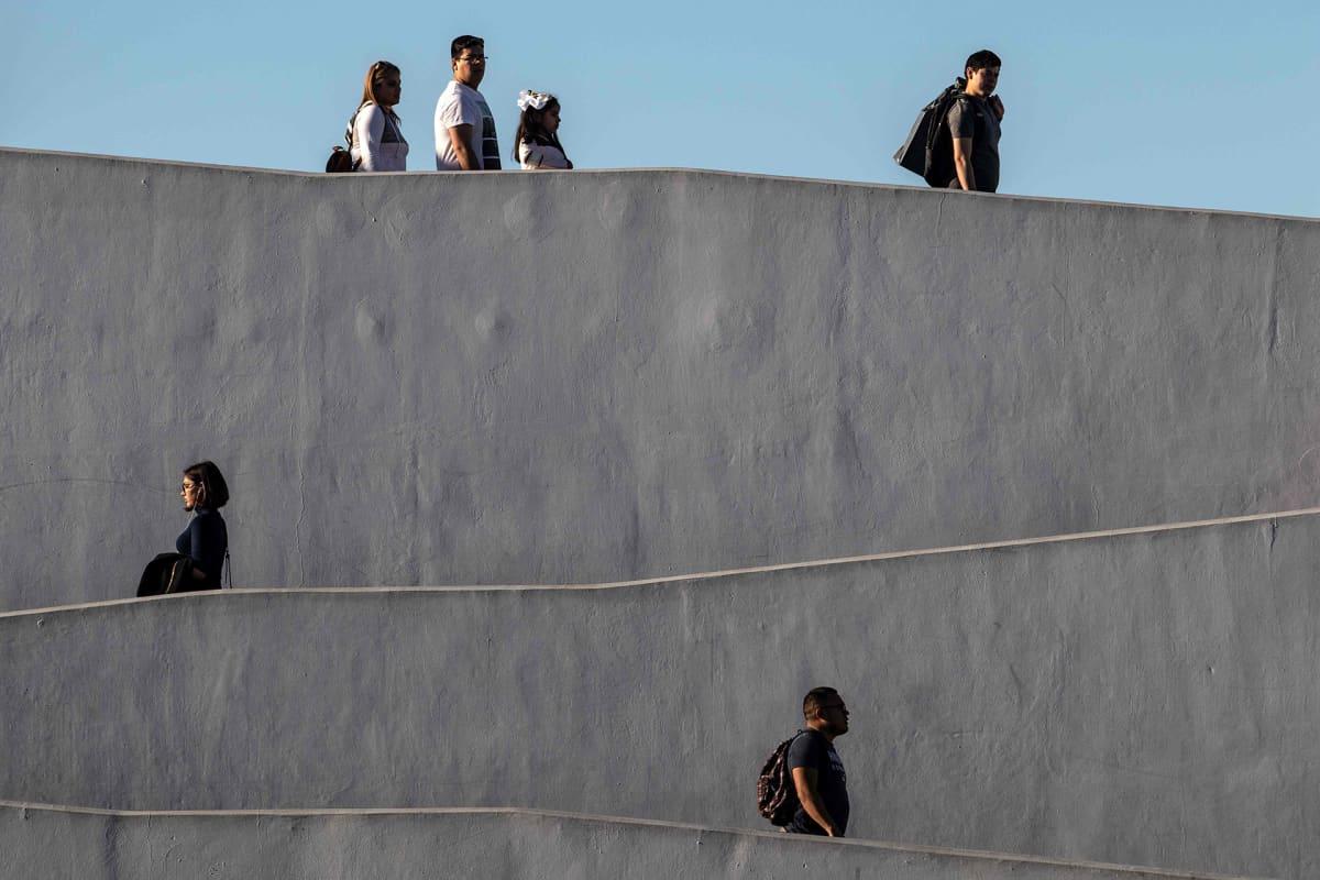 Siirtolaisia kävelysillalla.