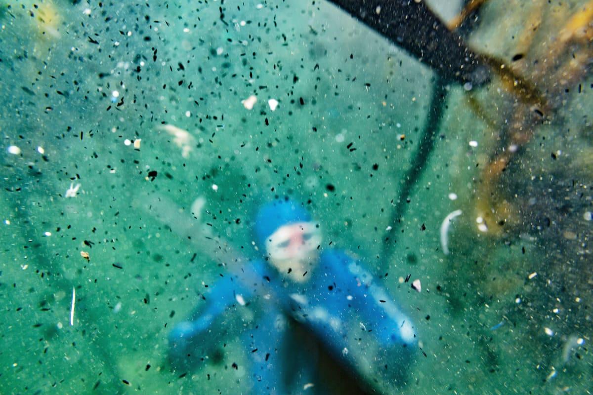 Sukeltaja meressä mikromuovin ympäröimänä.