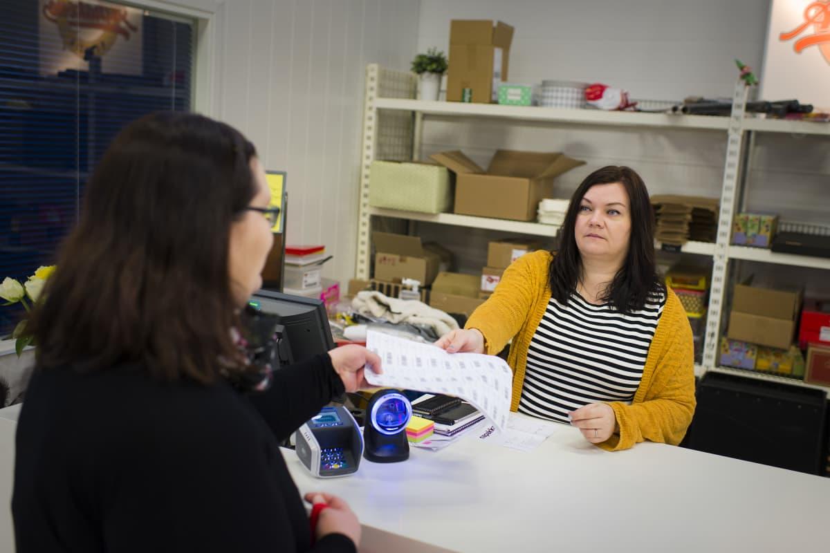 Tiina Mäkihonka palvelutiskin takana ojentaa papereita asiakkaalle.