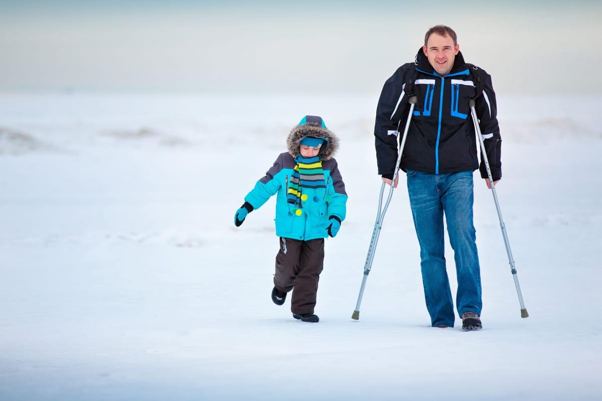 Isä kävelee kävelykeppien kanssa poika vierellään lumisessa maisemassa.