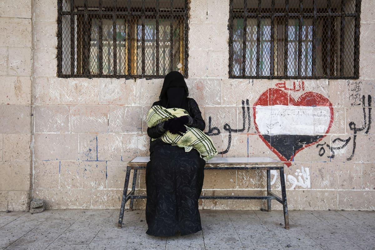 Jemeniläinen burkaan pukeutunut nainen vauva sylissään odottaa ruoka-apua.