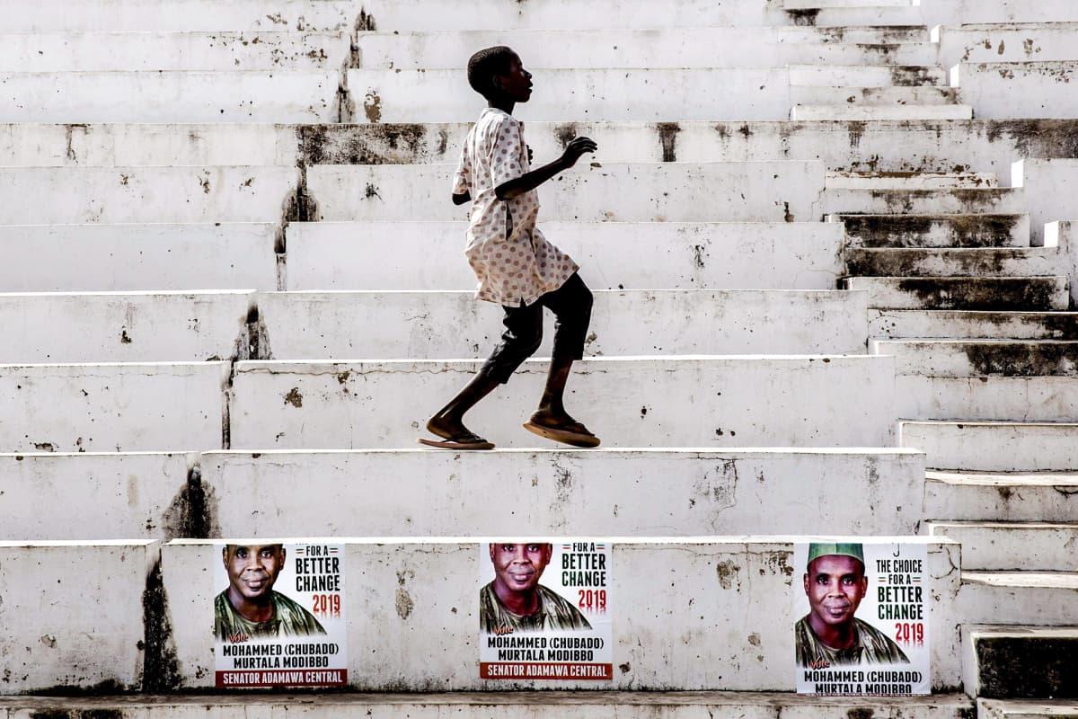 Poika tanssii valkoisilla portailla Jimetassa, Nigeriassa.