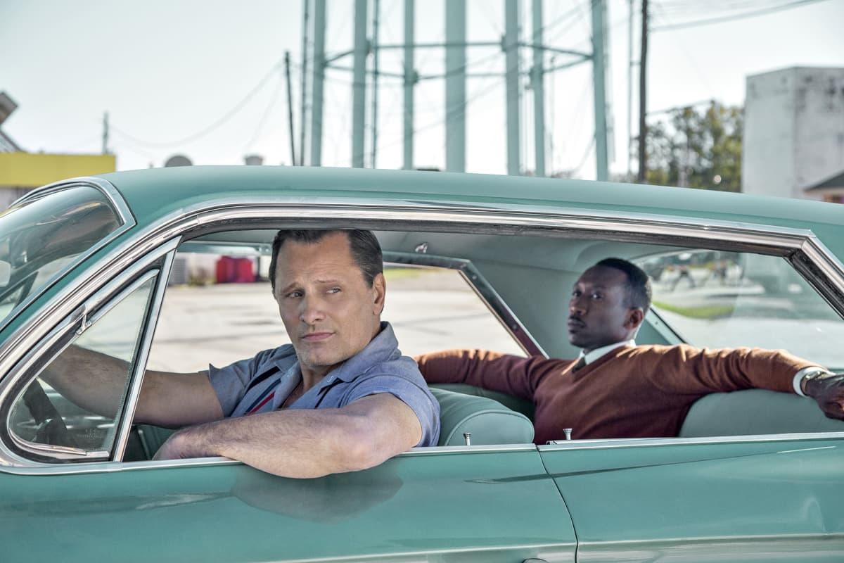 Näyttelijät Viggo Mortensen ja Mahershala Ali Green Book -elokuvassa. Elokuvastillissä valkoinen mies toimii autonkuljettajana mustalle pianistille 1960-luvun Yhdysvalloissa.
