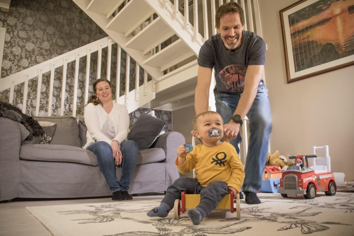 Äiti, isä ja taapero leikkivät olohuoneessa.