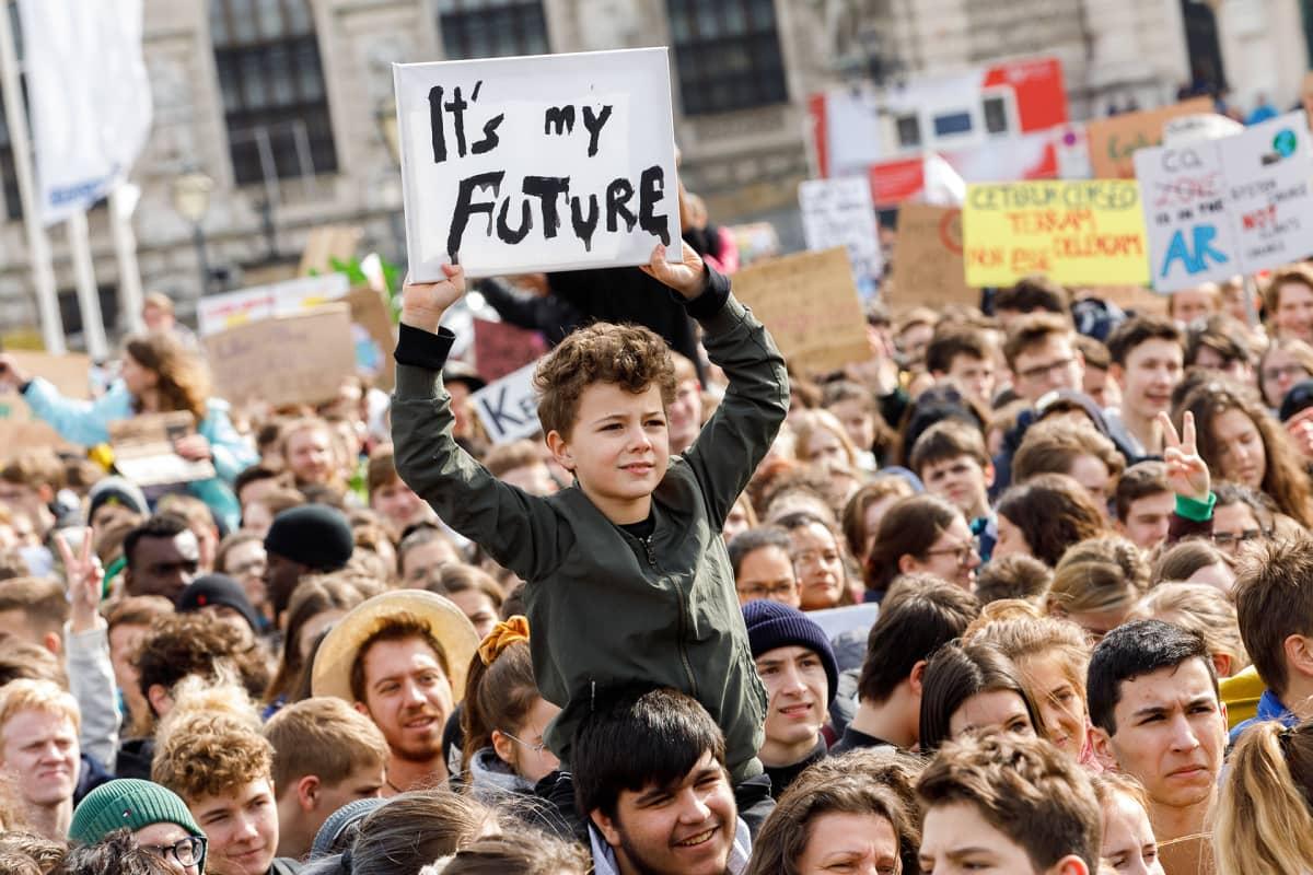 """Poika, jonka kyltissä lukee """"It's my future"""""""