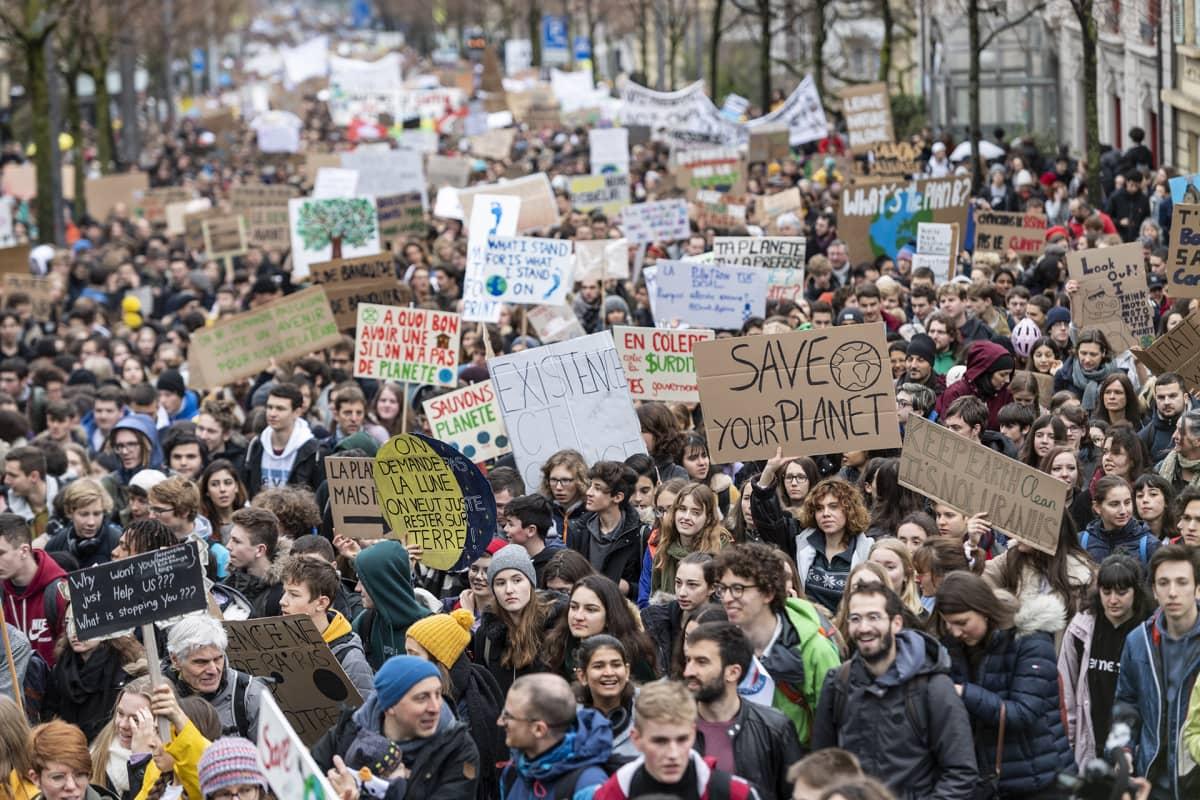 Suuri mielenosoittajajoukko etenee katua pitkin.