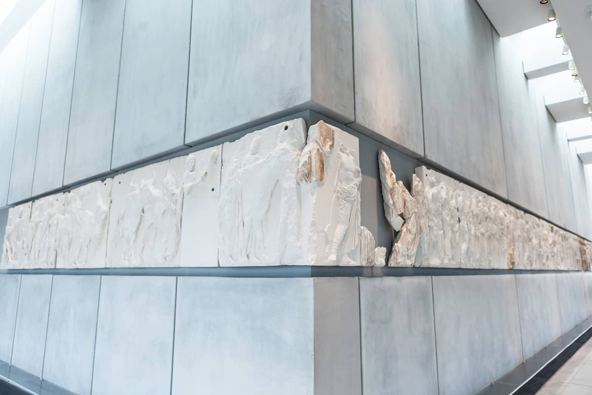 Parthenonin metrin korkuinen marmorifriisi kuvaa antiikin Panathenaia-juhlakulkuetta ratsumiehineen, juhlan osanottajineen ja uhrieläimineen. Valkoiset osat ovat Lontoon British Museumissa.