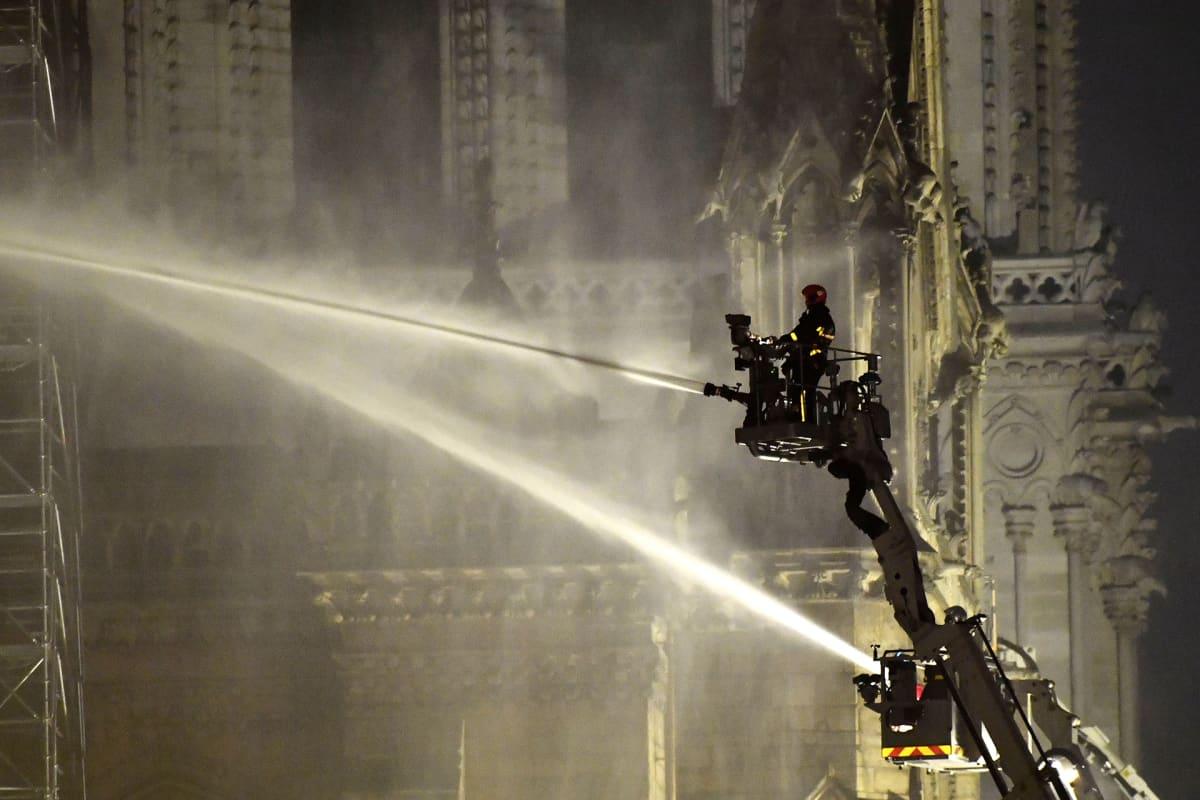 Palomiehiä nosturissa Notre Damen kattopalon sammutustöissä 15. huhtikuuta.