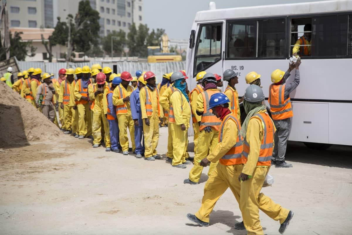 Qatarin pääkaupunkiiin Dohaan nousevaa toimistorakennusta rakentavat siirtotyöntekijät jonottavat bussista tarjoiltua lounasta.