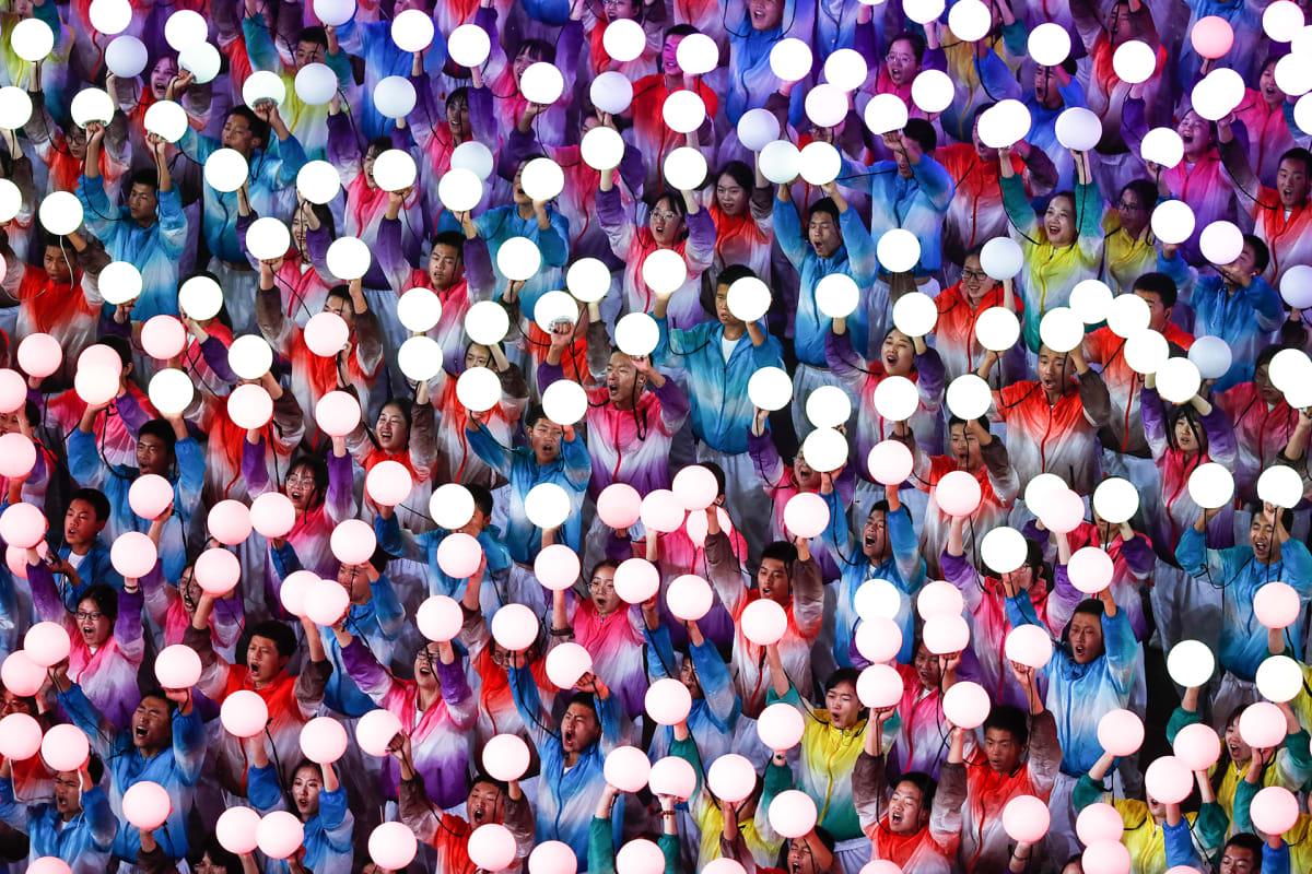 Kiinalaiset esiintyjät pitävät valopalloja iltahämärässä Pekingin kansallisella stadionilla.
