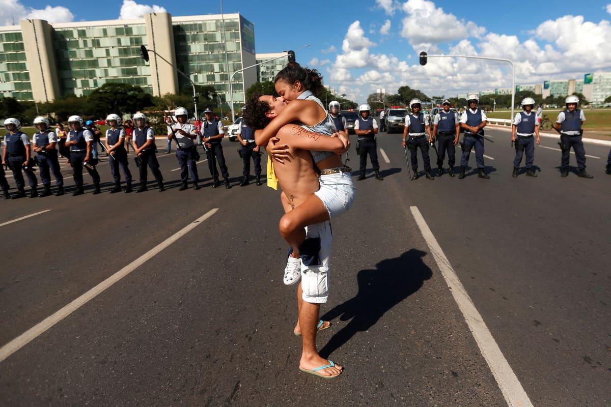 Nais- ja miesprotestoija suutelevat kiihkeästi poliisien edessä vastustaen Brasilian presidentti Jair Bolsonaron koulutusleikkauksia.