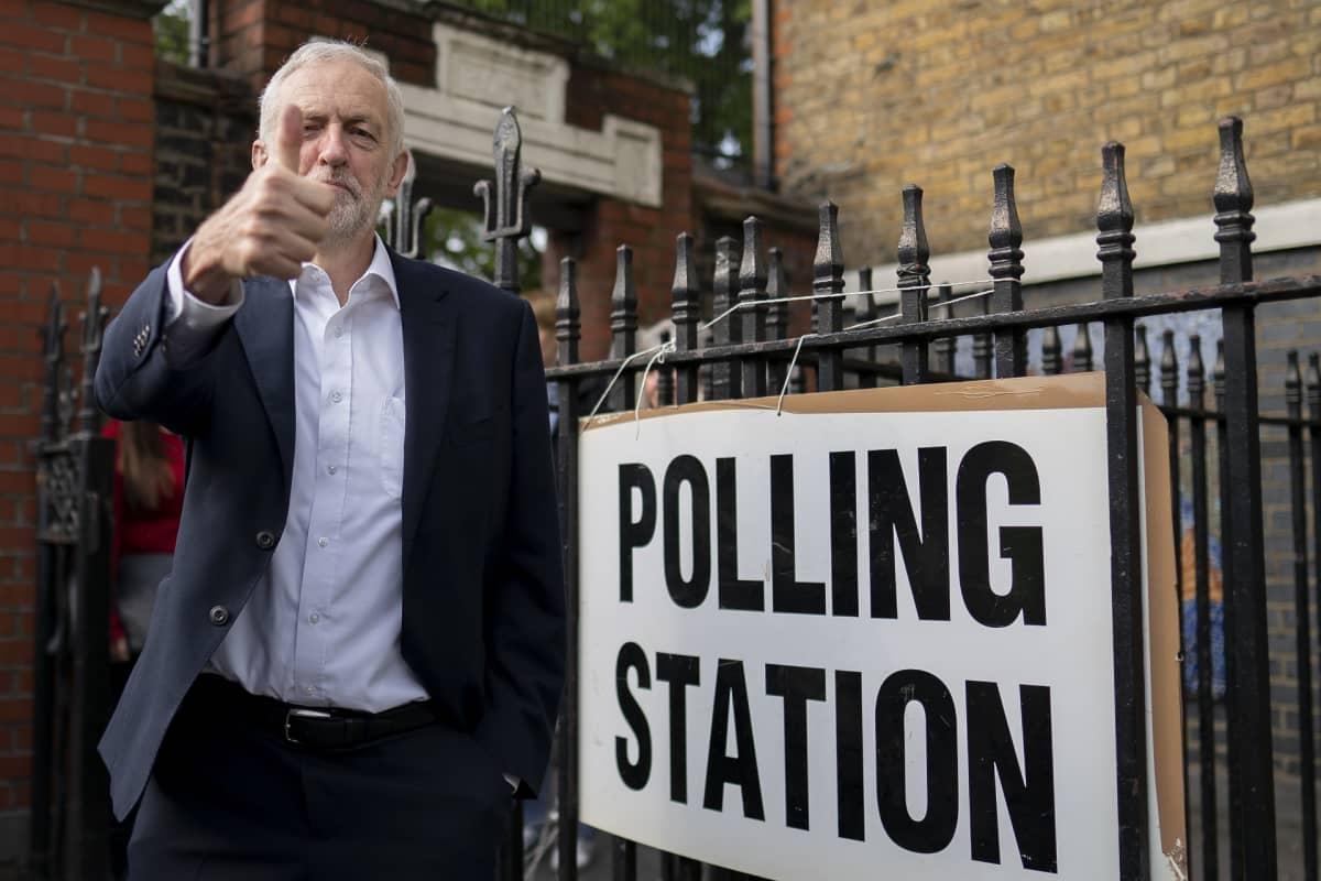 Jeremy Corbyn näyttää peukkua. Vieressä äänestyspaikan osoittava kyltti.