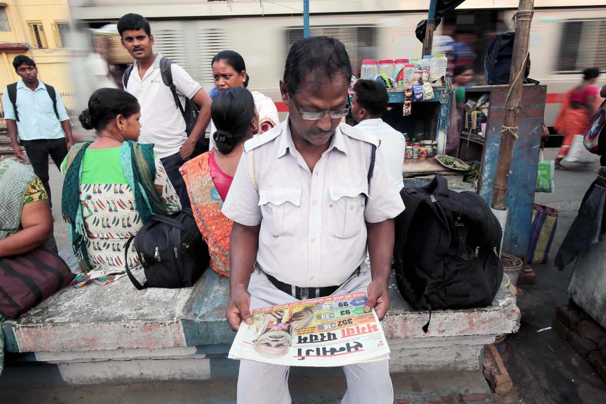 Poliisi lukee sanomalehdestä Narendra Modiista.