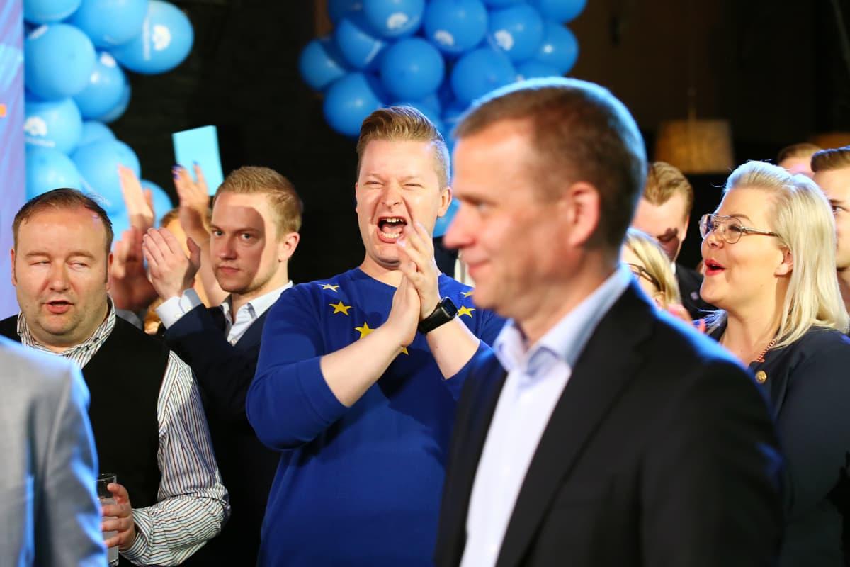 Kalle Lahtinen ja Piia Kurki taputtavat Petter Orpon taustalla kokoomuksen vaalivalvojaisissa.