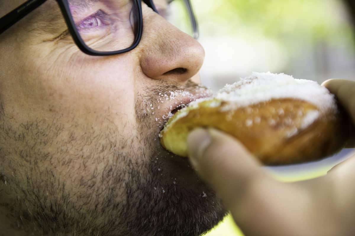 Mies syö sokeripullaa.