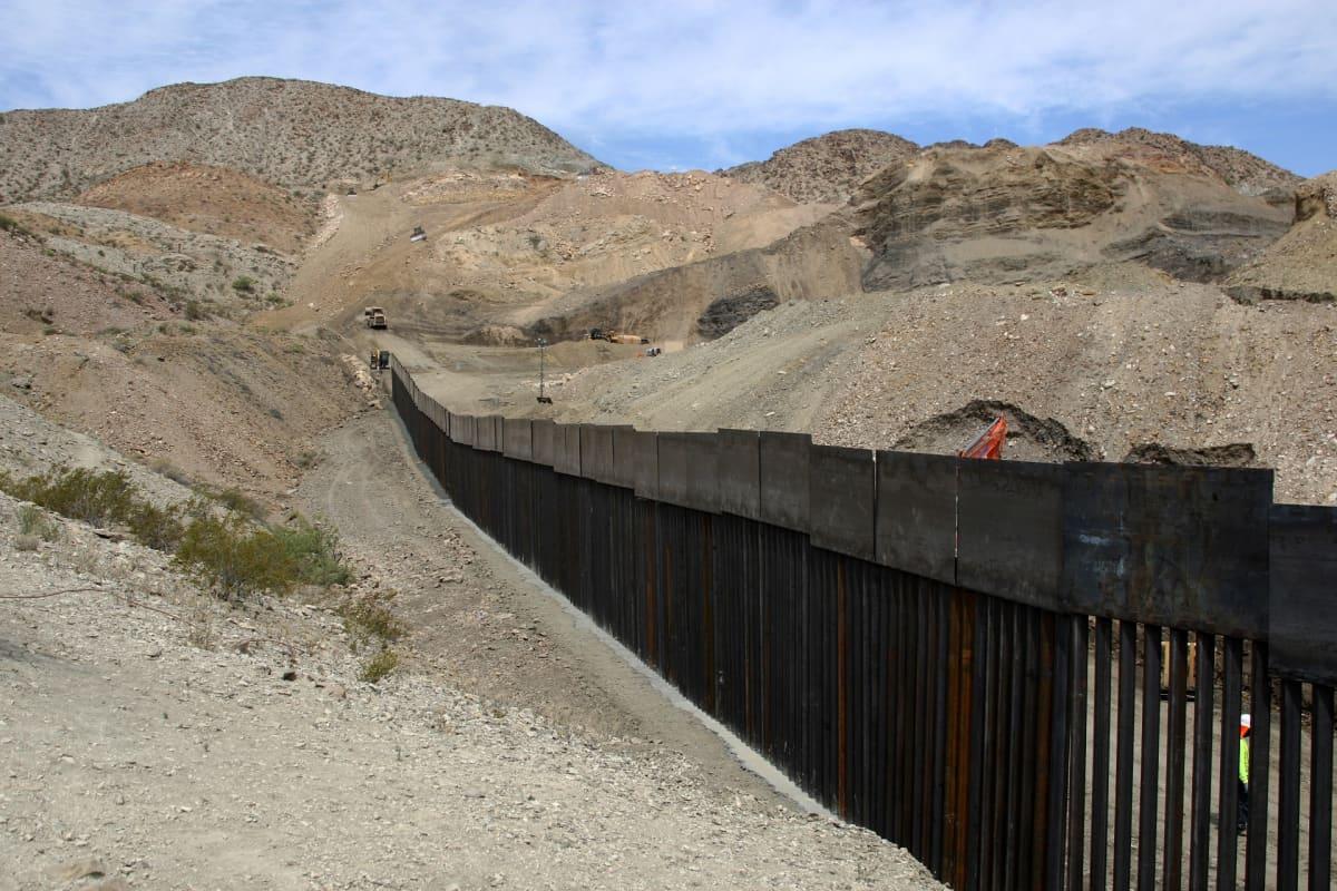 Rakenteilla oleva muuri karun maiseman keskellä.