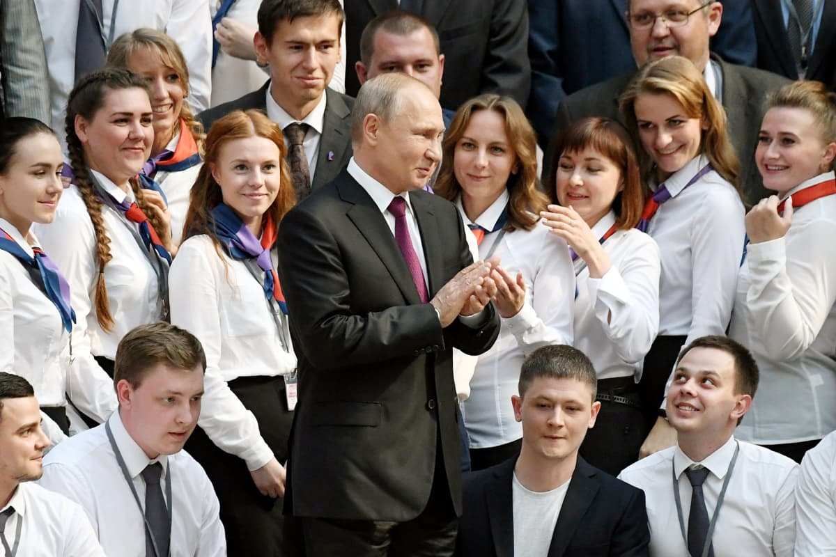 Vladimir Putin tervehtii Suora linja -ohjelman vapaaehtoisia puhelinpäivystäjiä Moskovassa.