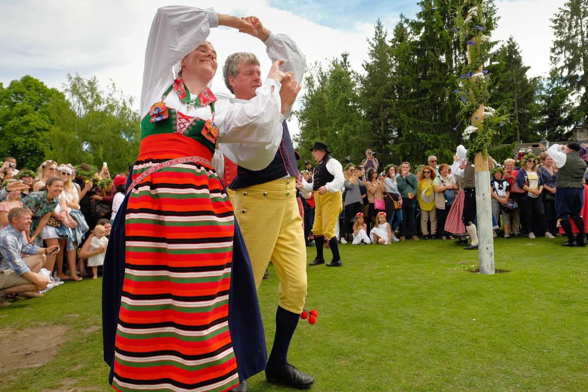 Kansallispukuihin pukeutuneet juhlijat tanssivat juhannussalon ympärillä Tukholmassa.