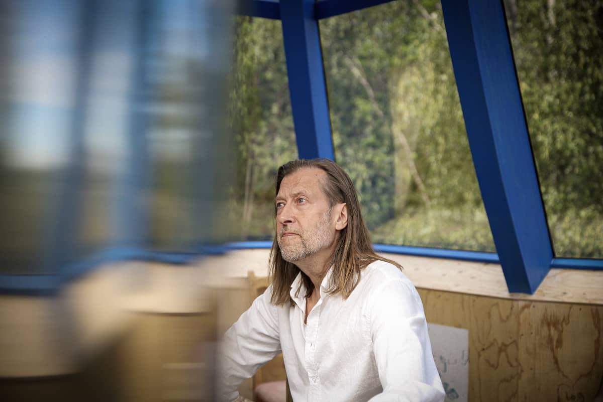 Taiteilija Jan-Erik Andersson istuu Lehtitalon ikkunan ääressä.