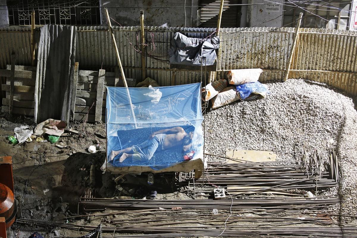 Mies nukkuu rakennustyömaalla.