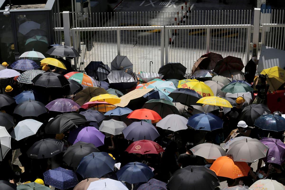 Demokratia-aktivistit ovat kokoontuneet sateenvarjojen kanssa hallintorakennuksen edustalle.