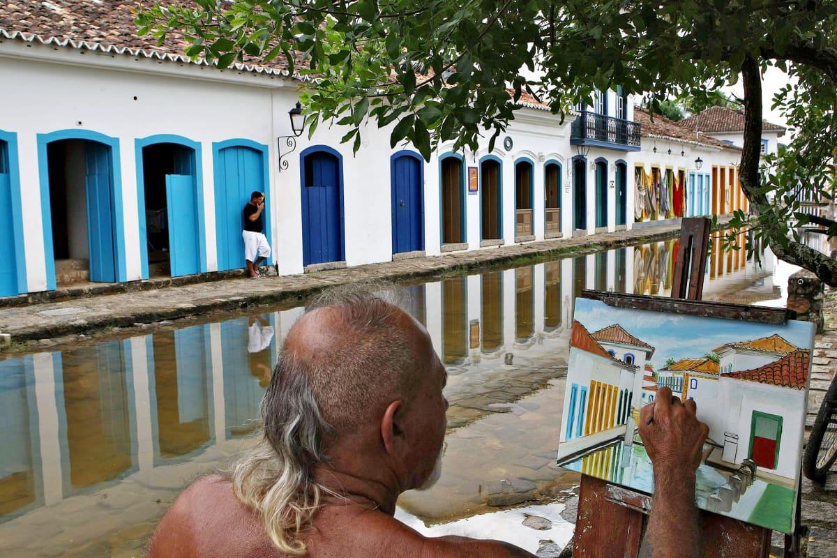 Mies maalaa puun varjossa katunäkymää Brasilian Paratyssa.