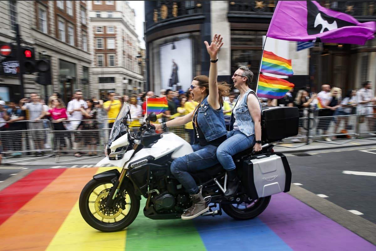 Kaksi naista moottoripyörän selässä.