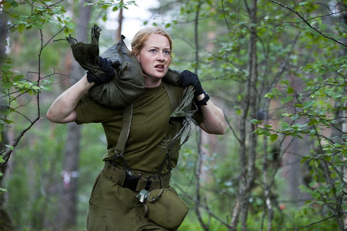 nainen kantaa säkkejä metsässä.