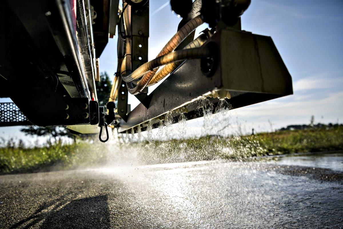 Noordenveldin kunnan tiekone tiputtaa suolavettä tienpinnalle Hollannin Noordenveldissa 24. heinäkuuta 2019.