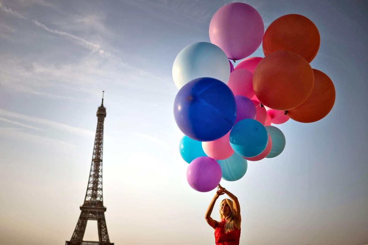Nainen poseraa ilmapallojen kanssa Pariisin helteissä 25. heinäkuuta 2019.