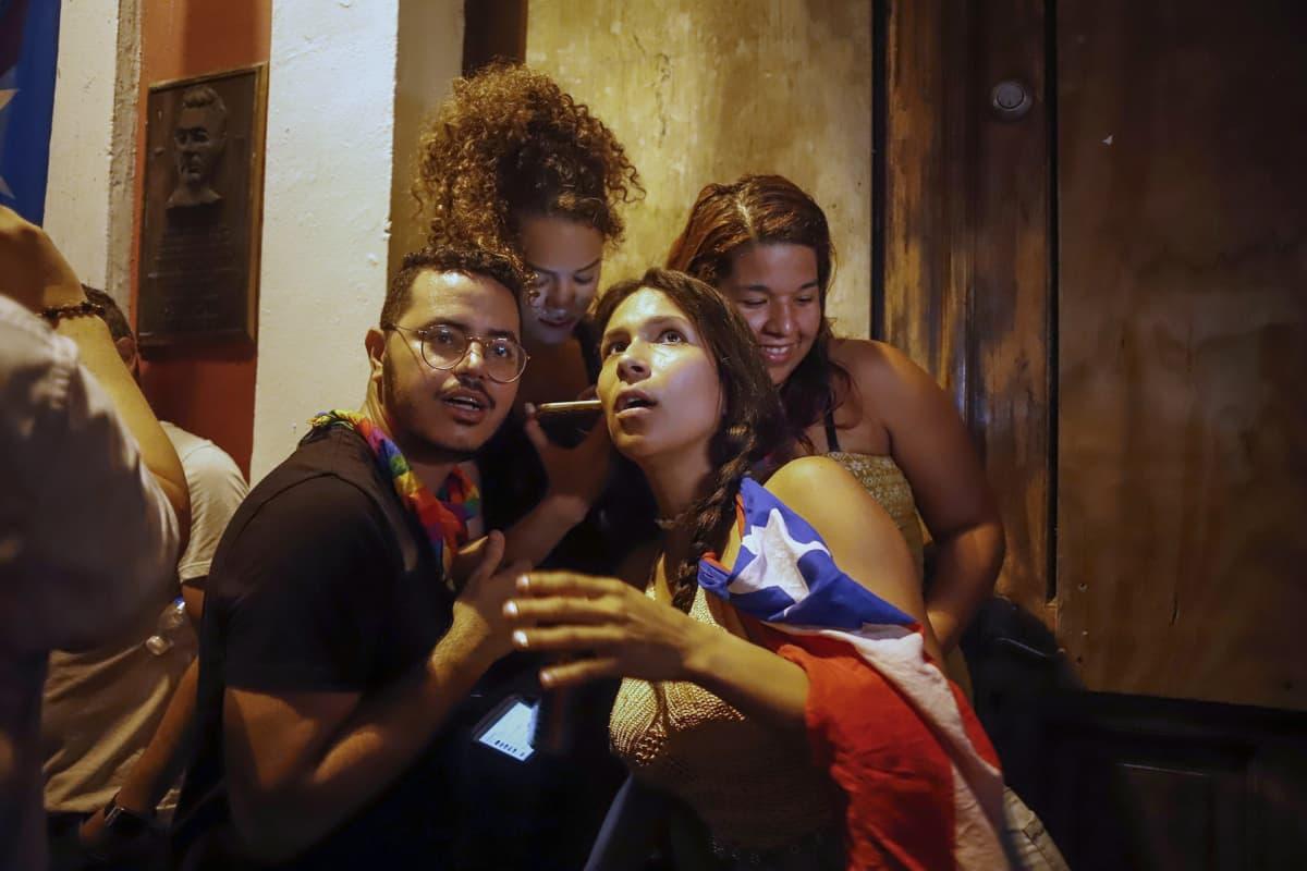 Neljä nuorta ihmistä kuuntelee Puerto Ricon kuvernöörin Ricardo Rossellon ilmoitusta kännykästä La Fortalezan vieressä, San Juanissa, Puerto Ricossa, 24. heinäkuuta 2019.