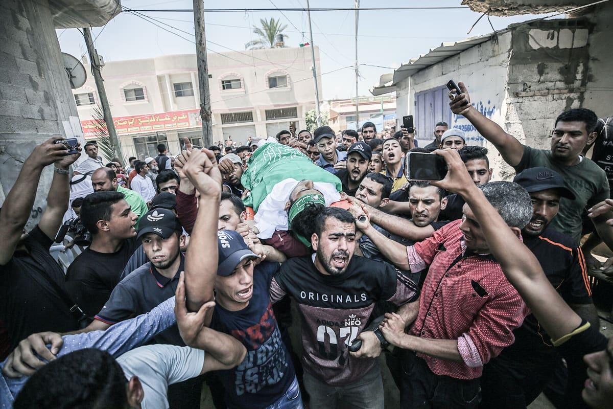 Palestiinalaiset kantavat 23-vuotiaan Ahmad Al-Qarran ruumista hänen hautajaisissaan Khan Younisissa, Gazassa 27. heinäkuuta.
