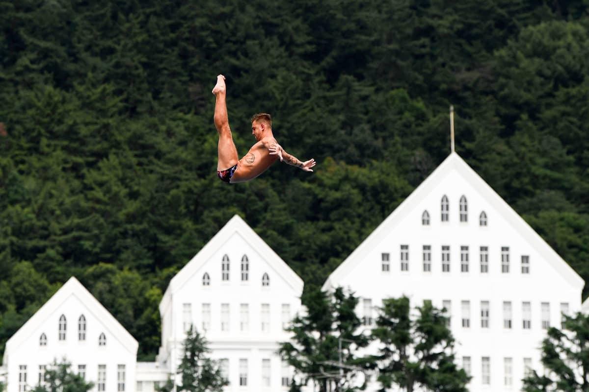 Venäläinen Nikita Fedotov ilmassa talojen kattojen yllä uimahyppyä suorittaen.