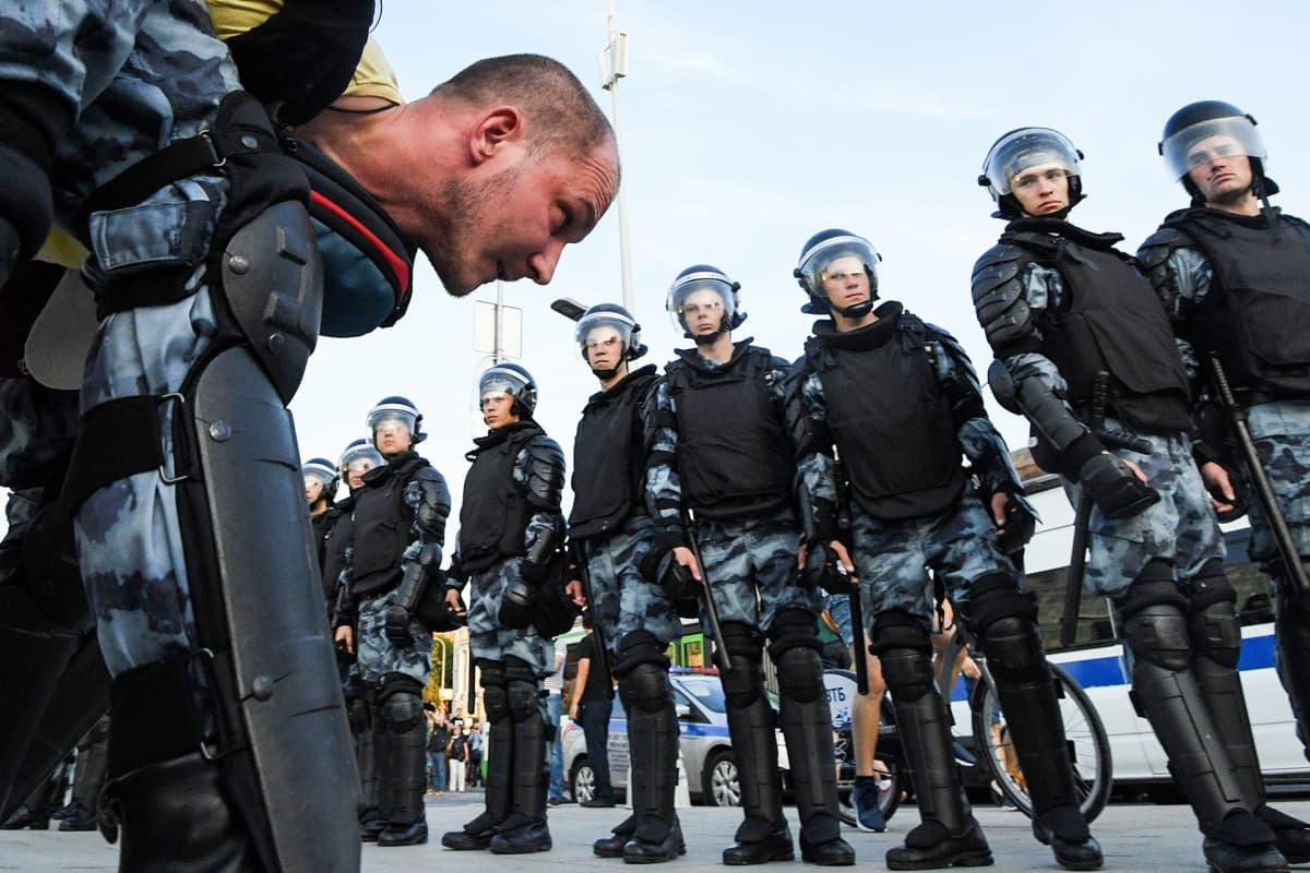 Poliisit tuijottavat pidätettyä mielenosoittajaa.