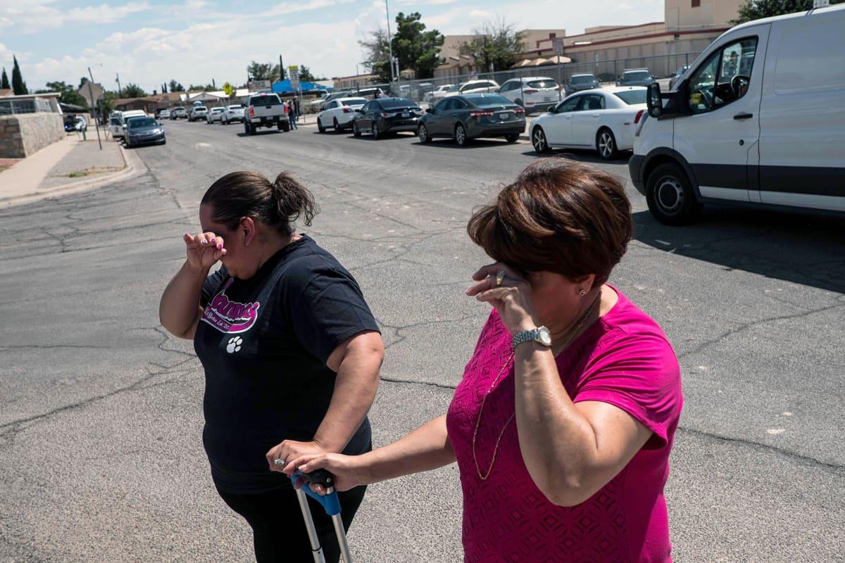 Kaksi naista itkee kadulla El Pasossa.