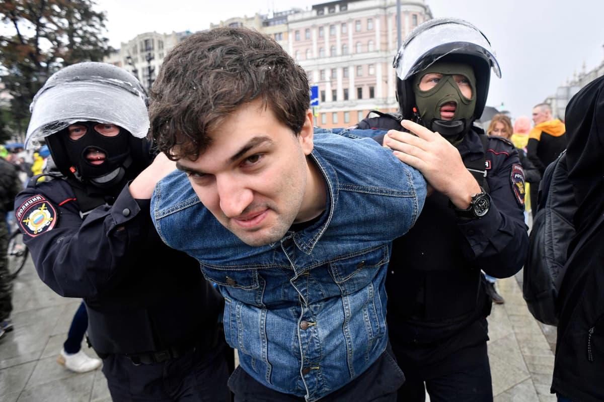 Mellakkapoliisit pitelevät kiinni nuorta miestä