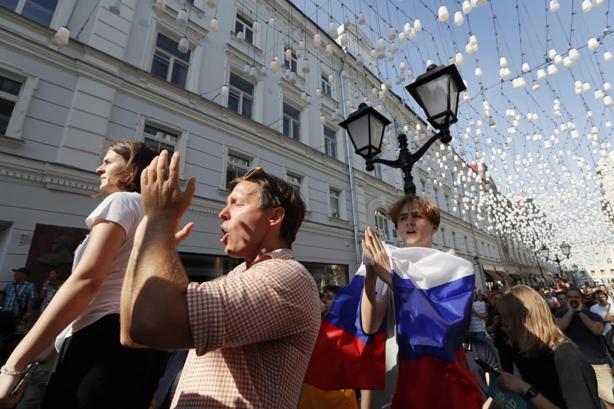 Mielenosoittajat taputtavat käsiään ja laulavat