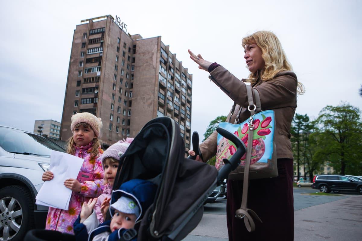 Antonina Jelisejeva ja hänen lapsensa etualalla, taka-alalla neuvostoaikainen rakennus.