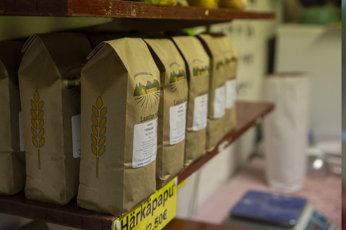 Tilojen suoramyyntiä on eri puolilla maata. Kuvassa tuusulalalisen Lassilan tilan myyntihylly, jossa on paperisia härkäpapupusseja.