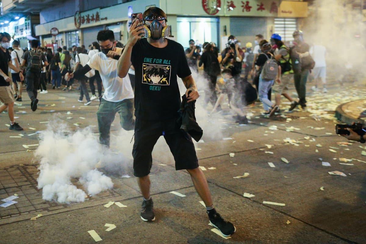 Protestoija kuvaa kännykällä poliiseja.