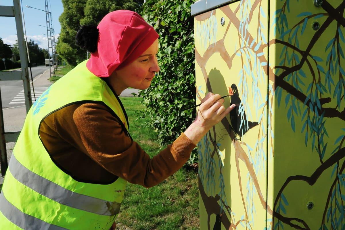 Elliina Peltoniemi maalaa lintuja sähkökaappeihin