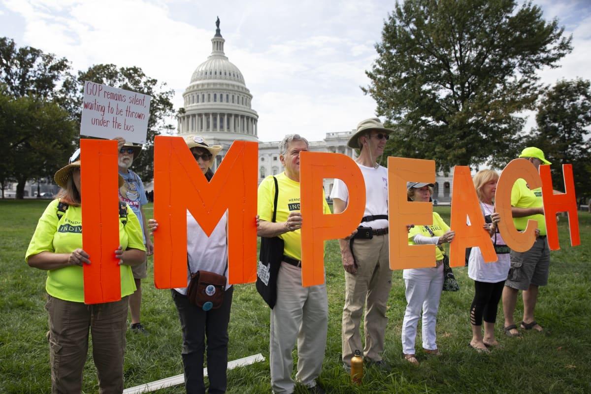 Joukko mielenosoittajia pitelee kirjaimia, joista muodostuu sana impeach.